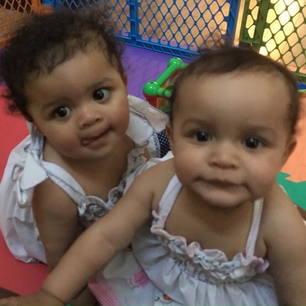 Image of two girls, Gabrielle and Penelope, playing in a play pen at an early child care facility.